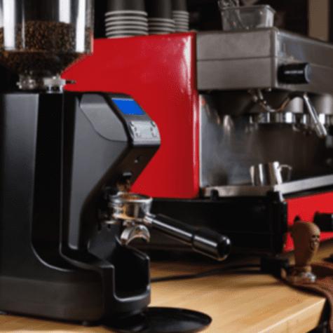 Moledora eléctrica de café, y máquina de café espresso en el fondo. </div>